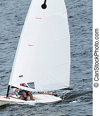 Small white sailboat racing in the sound close to New London...