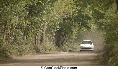 Small White Sedan Running on Gravel Forest Road Stirring Up...
