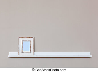 Small white shelf with picture frame on wall.