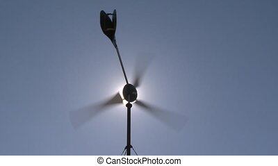 Small wind turbine spin and sun. Static shot.
