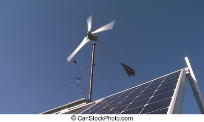 Small wind turbine with solar panel on blue sky background....