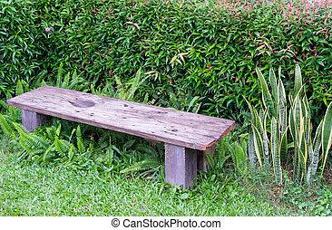 Small wooden bench in the backyard garden.