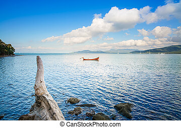 Small wooden boat and tree trunk in a sea bay on sunset. Punta Ala, Tuscany, Italy