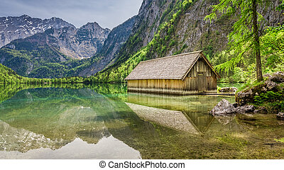Small wooden cottage and Obersee lake at spring, Alps, Germany