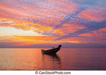 Small wooden fisherman boat at sunset