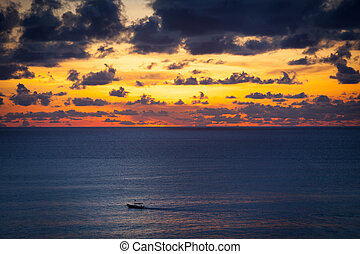 Small wooden fishing Boat at sunset in the ocean