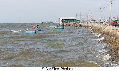 Small wooden fishing boats sway on the waves at the pier....