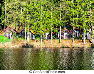 Small wooden forest cottages at the water