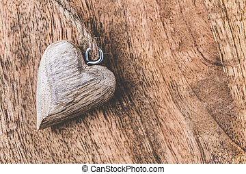 Small wooden heart on wooden background