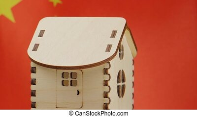 Small wooden house, China flag on background. Real estate concept, soft focus.