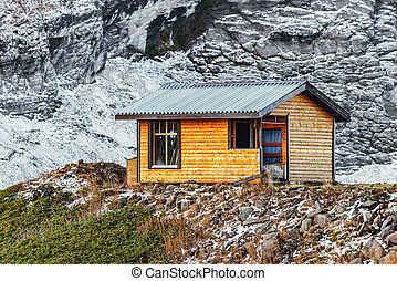 Small wooden house for the climbers on the mountain background.