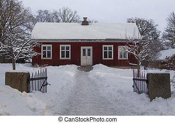 Small wooden red house covered by snow