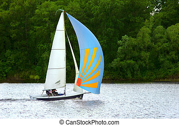 Small yacht sailing by the river with colorful blue sail