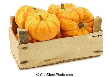 Small yellow and orange pumpkins in a wooden crate