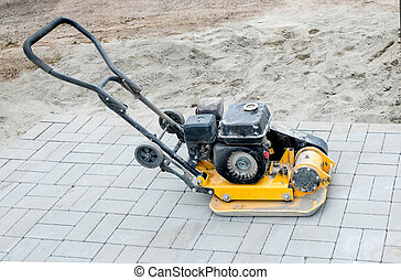 Small yellow compactor standing on new gray pavement