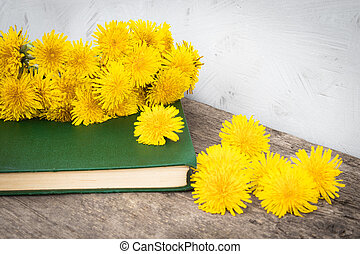 Small yellow dandelions lie on the old green paper on the background of old boards. There is a place for your text. Background.