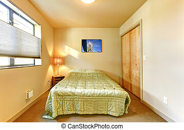 Small yellow guest bedroom interior.