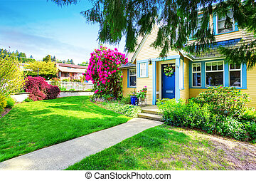 Small Yellow house exterior with blooming rhododendron