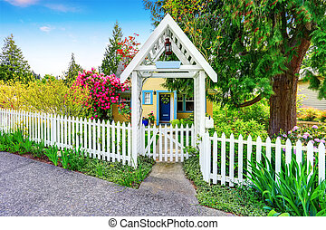 Small Yellow house exterior with White picket fence and ...