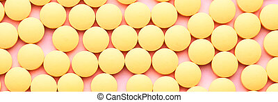 Small yellow pills on a pink background close-up.