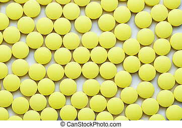 Small yellow pills on a white background close-up.