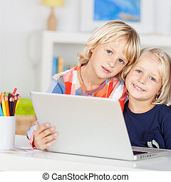 Small young girls smiling and using a laptop
