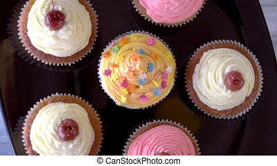 Small yummy desserts with frosting. Set of cupcakes with...