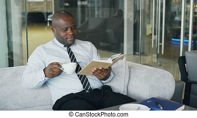 Smart African American businessman in formal clothes reading...