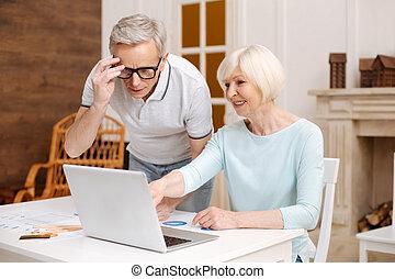 Smart analytical elderly gentleman having a look at the data