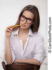 Smart and beautiful. Thoughtful young woman holding pencil near mouth and looking at camera while sitting on the chair