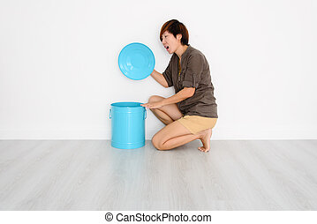 Smart Asian woman opening blue bin at home.