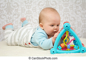 Cute baby lying on belly on soft surface and intently playing with her colorful toys.