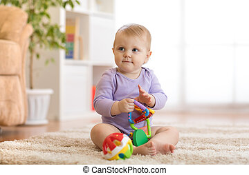 Smart baby with educatinal toys in sunny nursery room