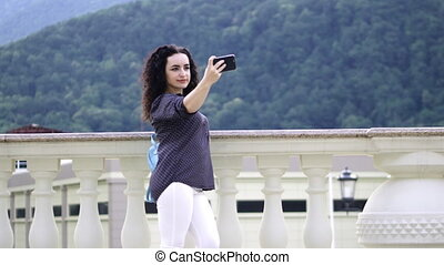 Smart, beautiful brunette corrects curly hair and makes selfie on a mobile phone against the background of outstanding mountains and beautiful sunset.