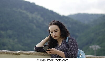 Smart, beautiful brunette corrects curly hair and prints sms on the phone at against the backdrop of outstanding mountains and beautiful sunset.