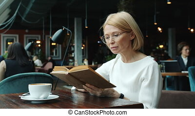 Smart business lady mature blonde reading book at table in ...