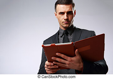 Smart businessman holding tablet computer over gray background