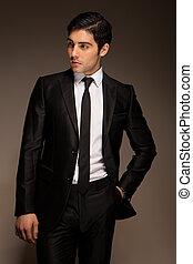 Smart Businessman standing and waiting in a three quarter pose dark studio portrait