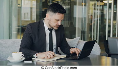 Smart Caucasian businessman using laptop computer and writing down information in his notepad in glassy cafe having coffee cup on his table.