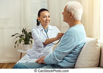Smart cheerful nurse using stethoscope - Medical...