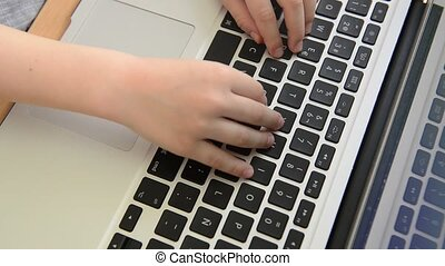 smart child plays with his fingers on the laptop in educational games