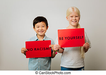 Smart children holding tables against racism in their hands