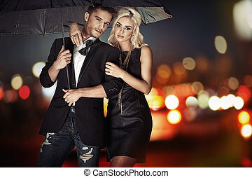 Smart couple walking with the umbrella