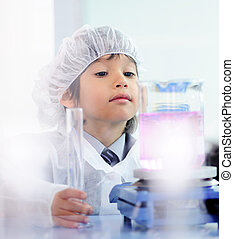 Smart cute little male child  experimenting with test tubes in real modern hospital lab