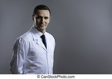 Smart doctor looking serious on a grey background