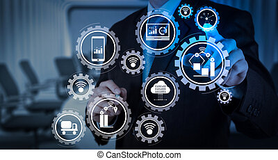 Smart factory and industry 4.0 and connected production robots exchanging data with internet of things (IoT) with cloud computing technology. Businessman hand pressing an imaginary button on virtual screen
