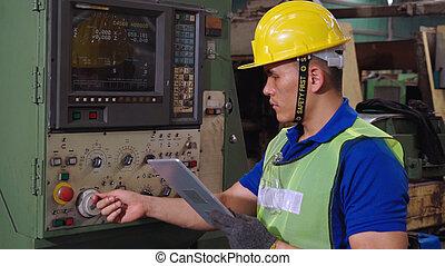 Smart factory worker using machine in factory workshop