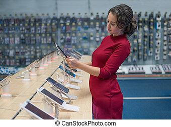 Smart female customer choosing digital tablet