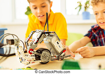 Close up of a robot being constructed by children