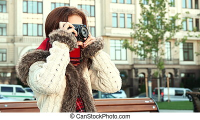 Smart girl adjusts the camera to take a picture